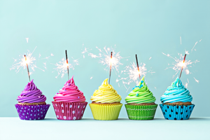 5 different colored cupcakes lined up with sparklers burning